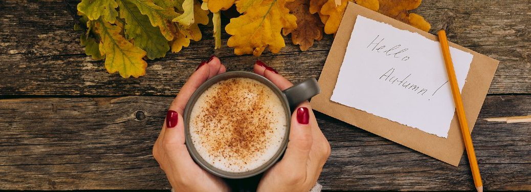 "Person's hands around a cup of latte with leaves and a note saying ""Hello Autumn!"" nearby"