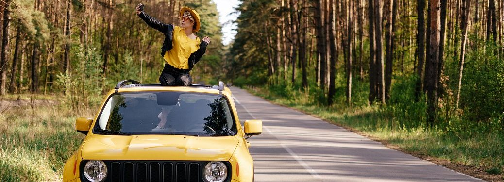Happy woman taking a selfie out of the sunroof of a yellow car
