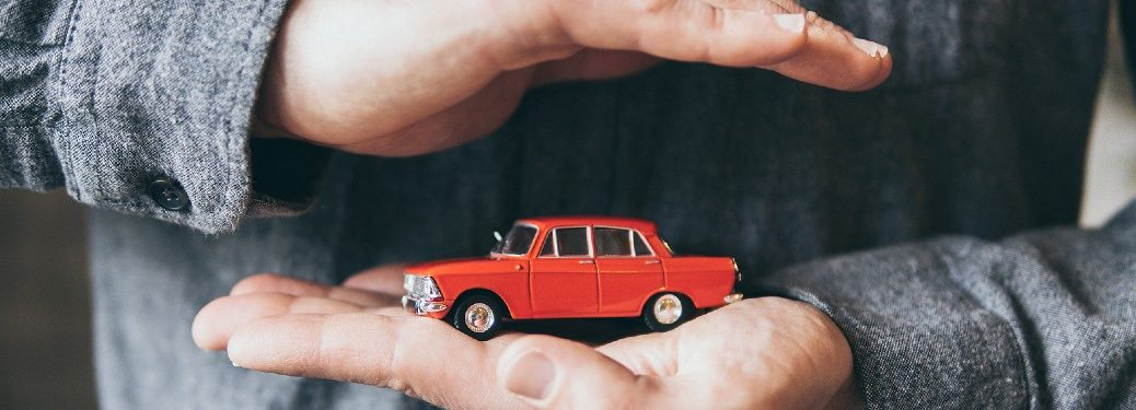 Hands holding a red toy car