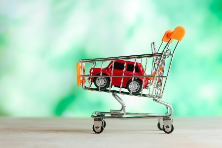 Red toy car inside of a toy shopping cart