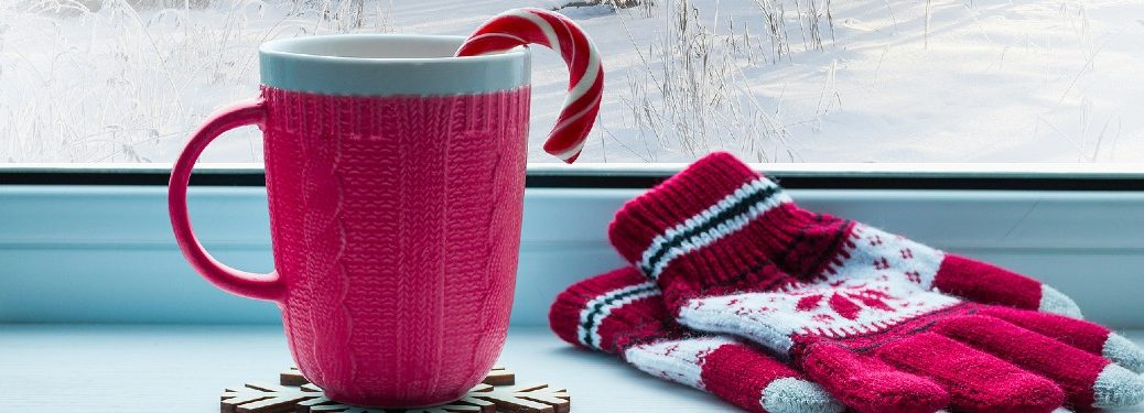 Red mug and gloves by a window with snow outside