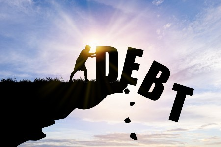 """Graphic of a person pushing the word """"Debt"""" off a cliff"""