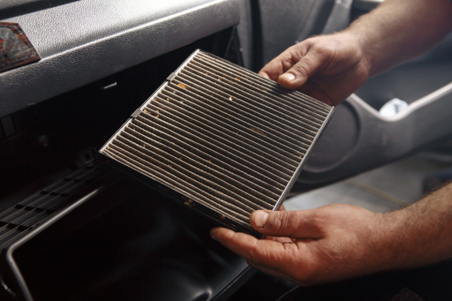 Person holding a dirty air filter