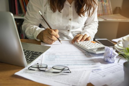 Woman with some paperwork and a calculator