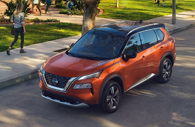 Front driver angle of an orange 2021 Nissan Rogue