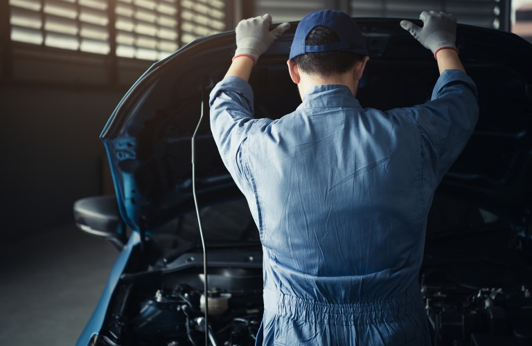 Mechanic looking under the hood of a car