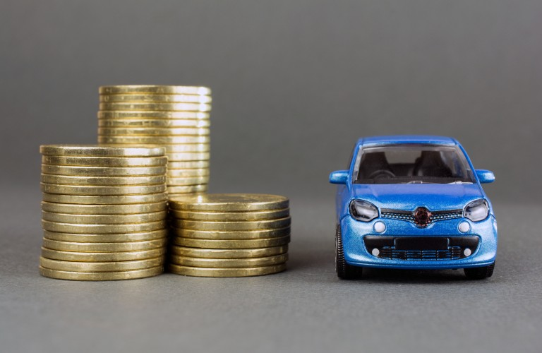 Stack of coins next to a blue toy car