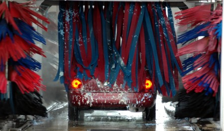 Red car going through an automated car wash