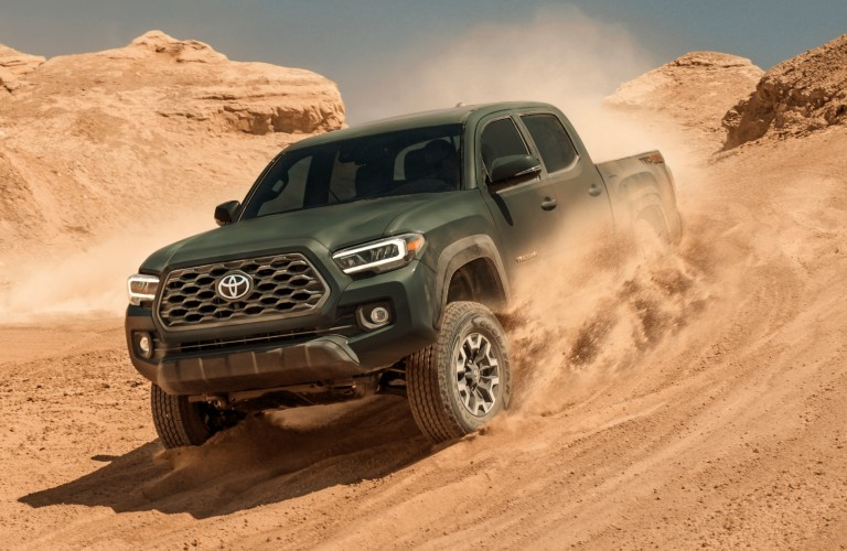 Green 2021 Toyota Tacoma driving in sand