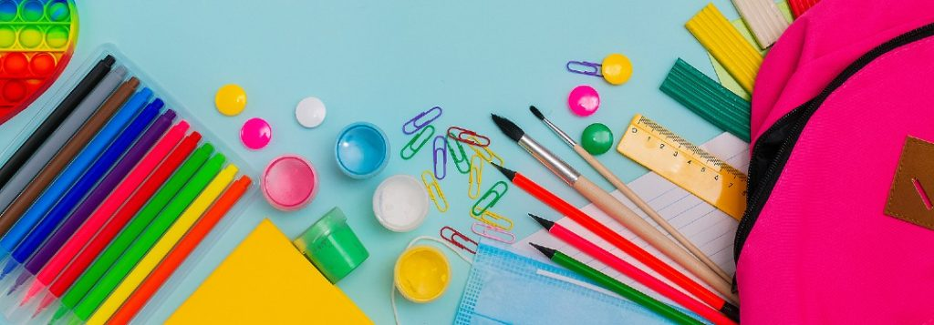 Colorful school supplies on a blue background