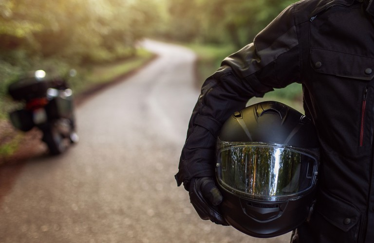 Person holding a motorcycle helmet with a motorcycle in the background