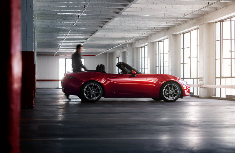red mazda miata convertible parked inside by windows