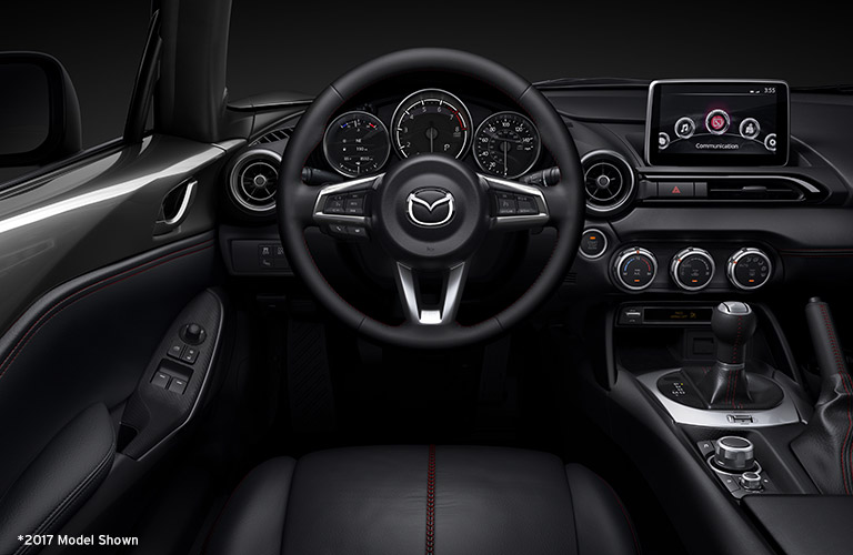 View of 2018 Mazda MX-5 MIata black interior and steering wheel and infotainment system