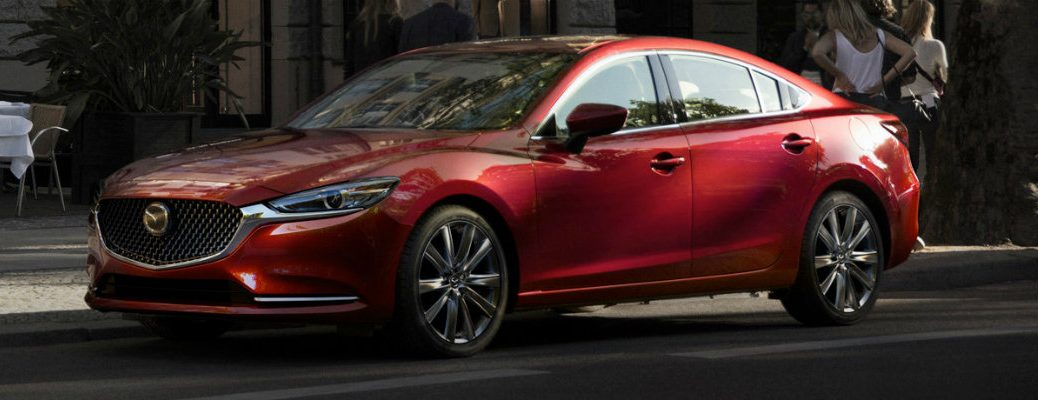 Exterior view of a red 2018 Mazda6 parked curbside in the city with a group of people nearby