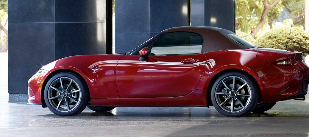 Exterior view of a red 2019 Mazda MX-5 Miata parked outside an office building