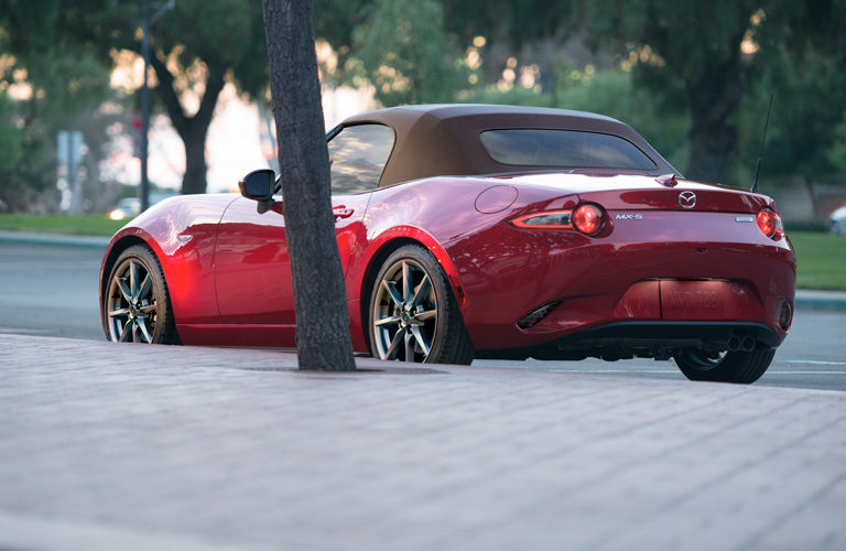 Exterior view of a red 2019 Mazda MX-5 Miata parked curbside on a sunny day