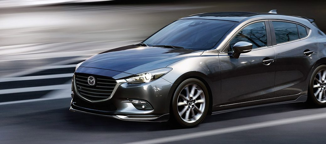 Exterior view of a dark gray 2018 Mazda3 driving down a city street