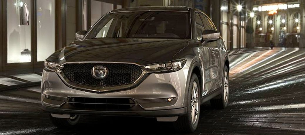 Exterior view of a silver 2019 Mazda CX-5 driving down a city street