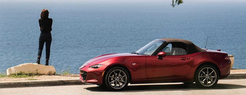 Exterior view of a red 2019 Mazda MX-5 Miata parked on the shoulder of a costal highway with a woman looking out over the water