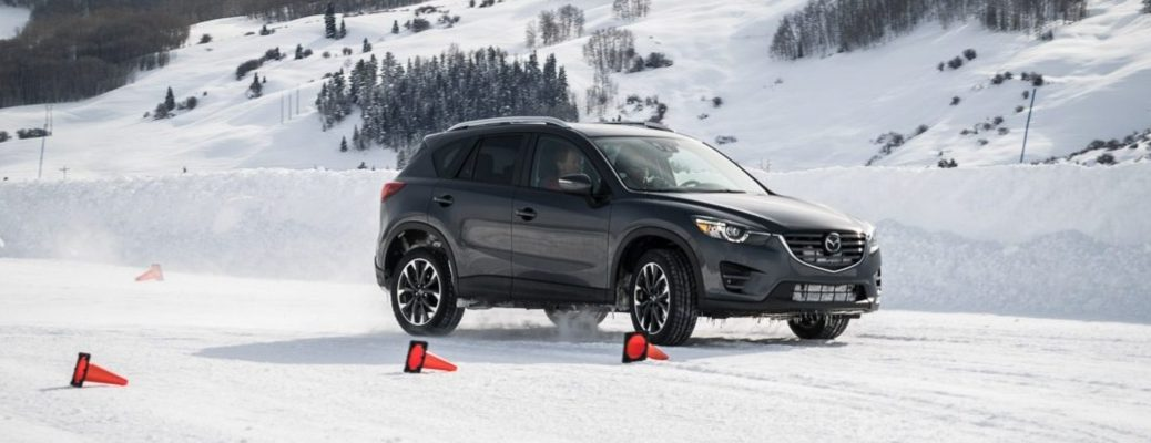 Exterior view of a black Mazda crossover driving on snow-covered terrain to test the i-ACTIV AWD system