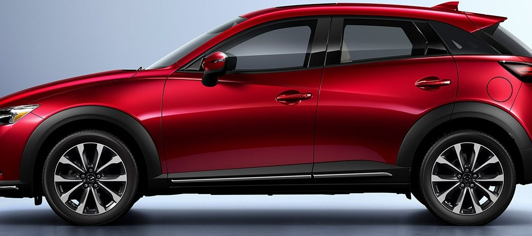 Side view of a red 2019 Mazda CX-3 parked in a silver showroom