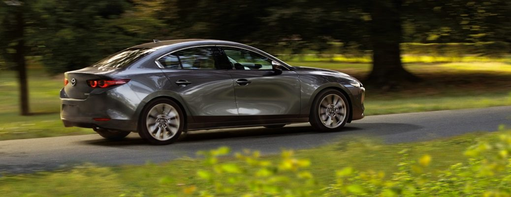 Exterior view of a gray 2019 Mazda3 Sedan driving down a suburban street