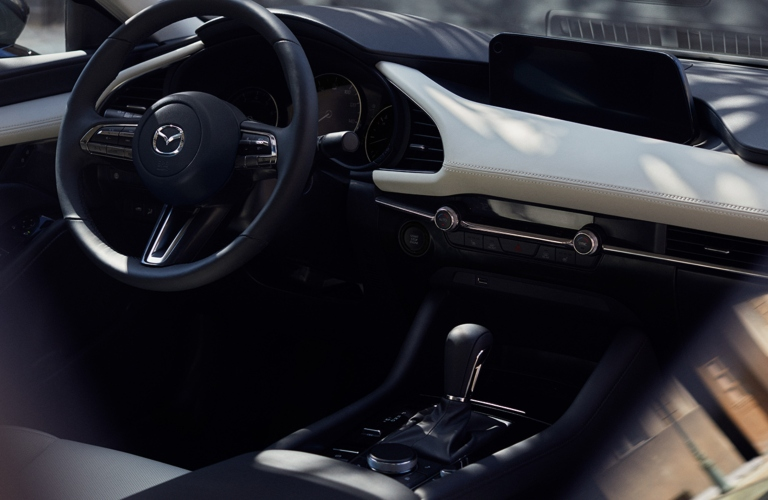 Interior view of the steering wheel and gear stick inside a 2019 Mazda3 Sedan