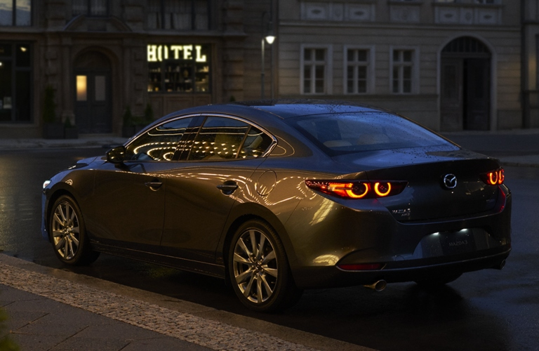 Exterior view of the rear of a gray 2019 Mazda3 parked on a city street