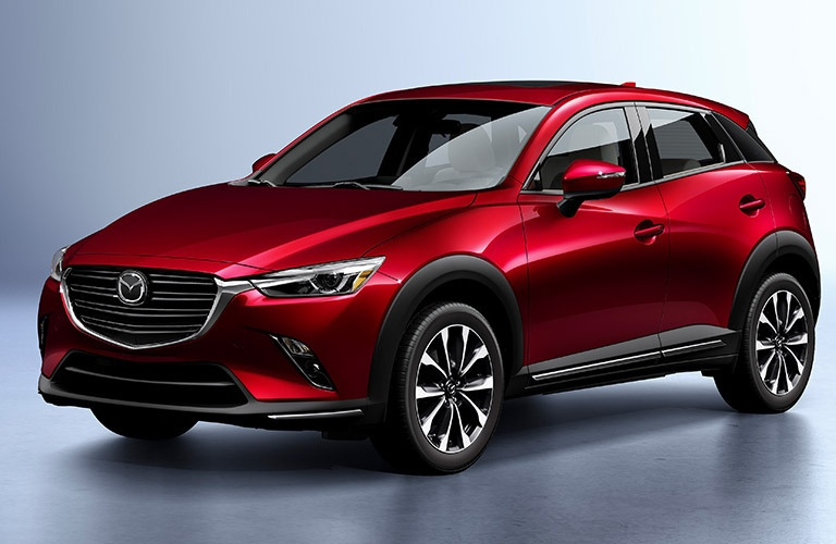 Exterior view of the front of a red 2019 Mazda CX-3 parked in a silver showroom