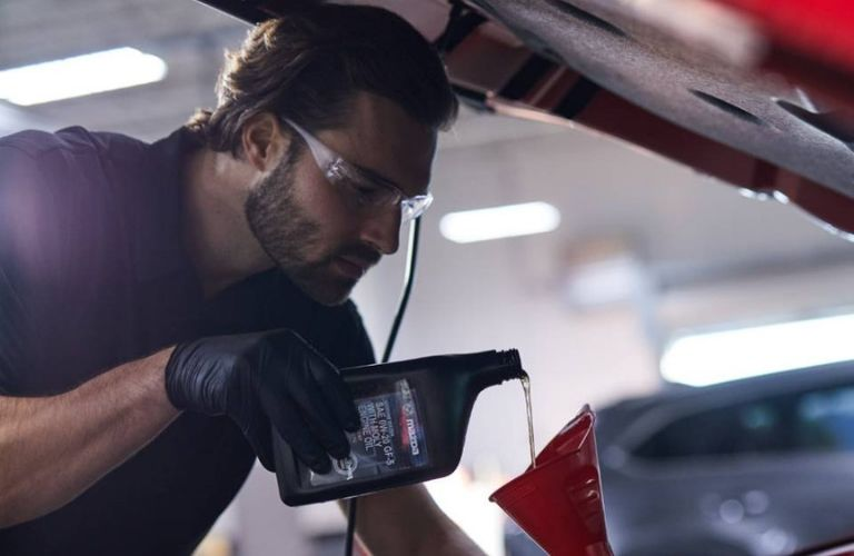 Image of a Mazda service technician changing the oil in a Mazda vehicle