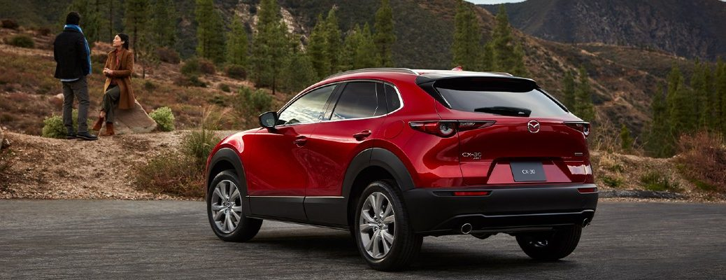 2020 Mazda CX-30 red paint parked by mountain forest trail view of back end and asphalt