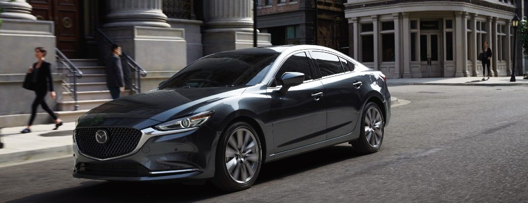 2020 Mazda6 silver paint driving down city street showing front and driver side doors facing left