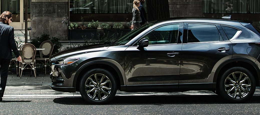 A grey Mazda CX-5 waiting for a pedestrian to pass