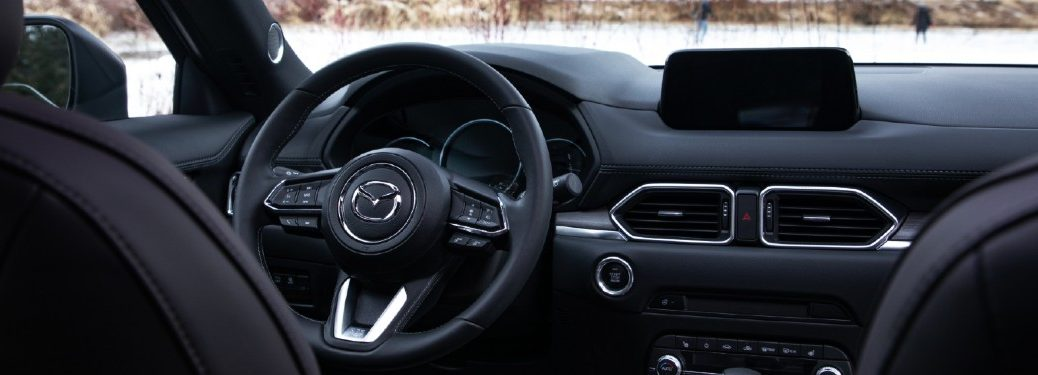 The interior front view of a 2020 Mazda CX-5 Signatureparked in a snowy area