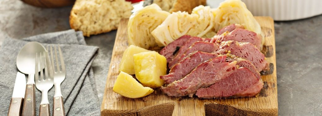 Corned beef and cabbage meal on a wood tray.