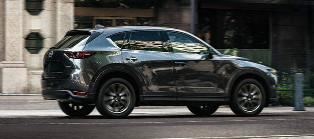 A gray 2020 Mazda CX-5 driving down a city road.