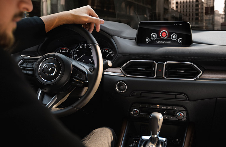 The interior view of a man driving a 2020 Mazda CX-5 with the steering wheel and touchscreen displayed.