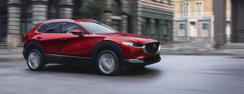 A red 2020 Mazda CX-30 driving down a city setting.
