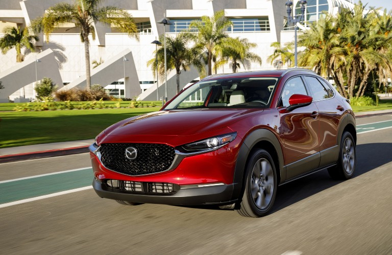 A red 2020 Mazda CX-30 driving down an open road in a beach-like setting.