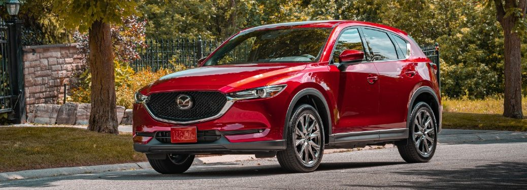 A red 2020 Mazda CX-5 parked in a lightly forested area.