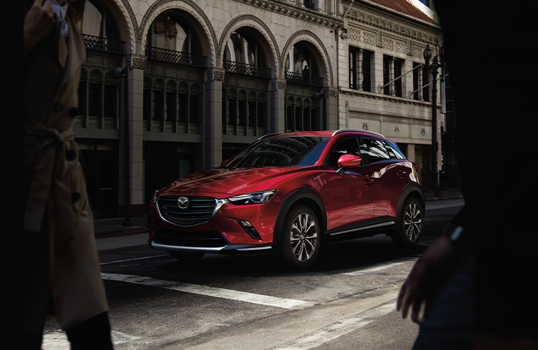 A front and side view of a red 2020 Mazda CX-3 parked at a stop light in a city.