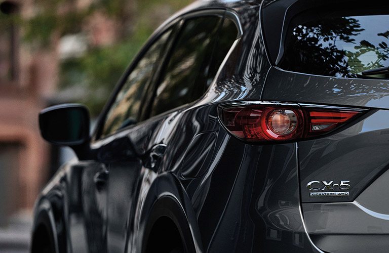The rear and side view of a gray 2020 Mazda CX-5.
