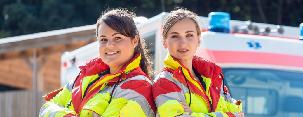 A pair of female paramedics standing back to back in front of an ambulance.