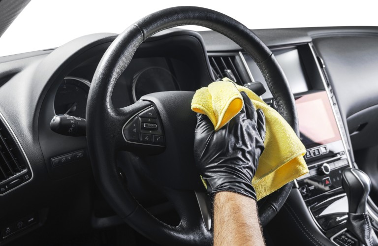 A person with a black glove on wiping down a steering wheel with a yellow cloth.