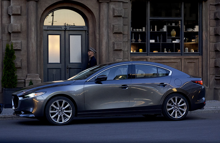 The side image of a gray 2020 Mazda3 Sedan parked next to a doorway.