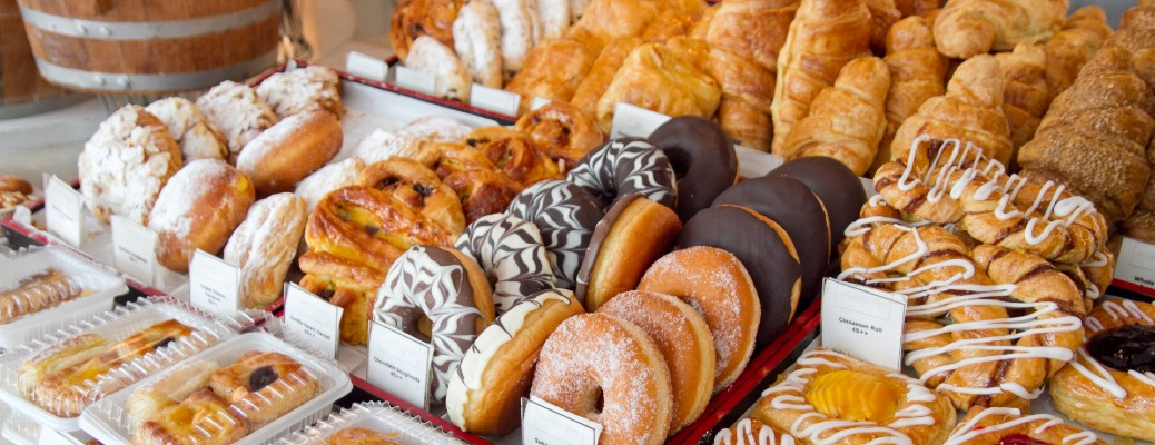 An assortmant of donuts and other baked goods at a bakery.