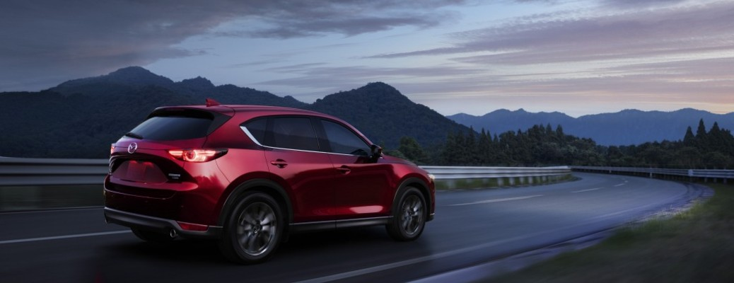 The rear and side view of a red 2021 Mazda CX-5 driving down an open road.