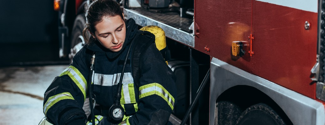 A tired female firefighter sitting next to a firetruck.