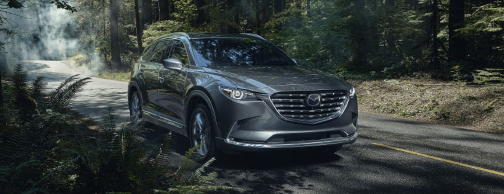 The front of a gray 2021 Mazda CX-9 driving through a covered forest.