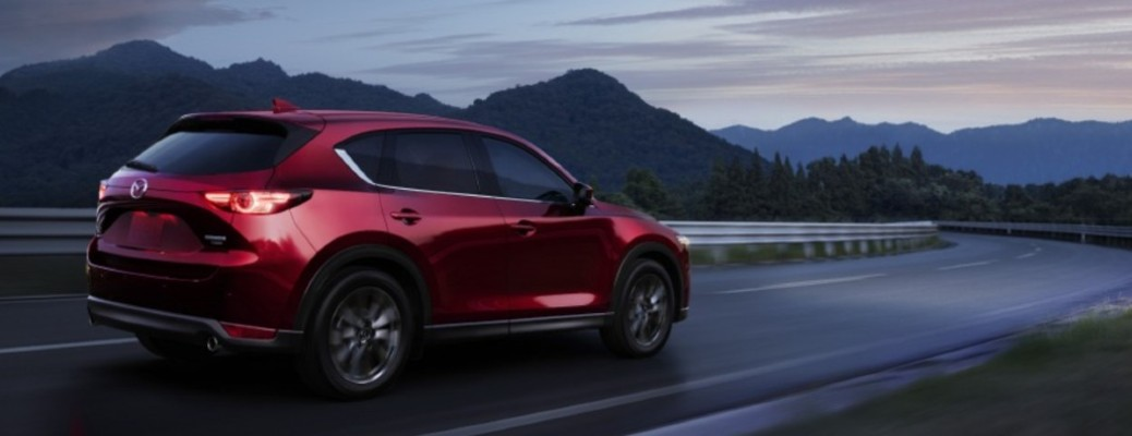The side and rear of a red 2021 Mazda CX-5 driving down a road.